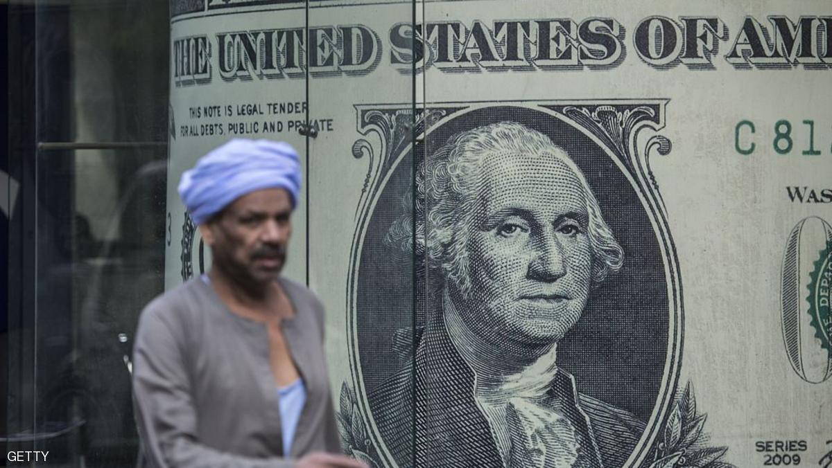 A man walks past a currency exchange shop displaying a giant US dollars banknote in downtown Cairo on November 3, 2016. Egypt floated the country's pound as part of a raft of reforms, after a dollar crunch and exorbitant black market trade threatened to grind some imports to a halt. / AFP / KHALED DESOUKI        (Photo credit should read KHALED DESOUKI/AFP/Getty Images)